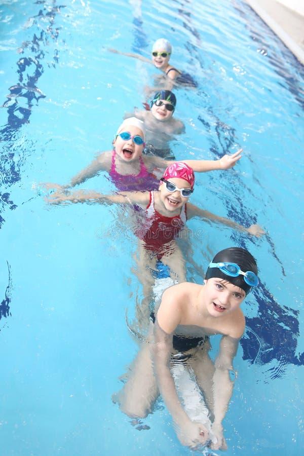 Niños que nadan en piscina imagen de archivo