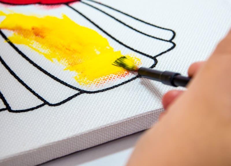 niños que pintan color amarillo en lona foto de archivo