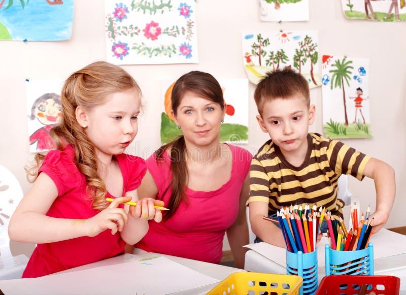 Niños que pintan con el profesor. imágenes de archivo libres de regalías
