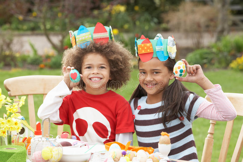 Niños que pintan los huevos de Pascua en jardines fotos de archivo