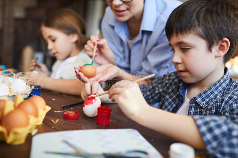 Niños que pintan los huevos de Pascua fotos de archivo