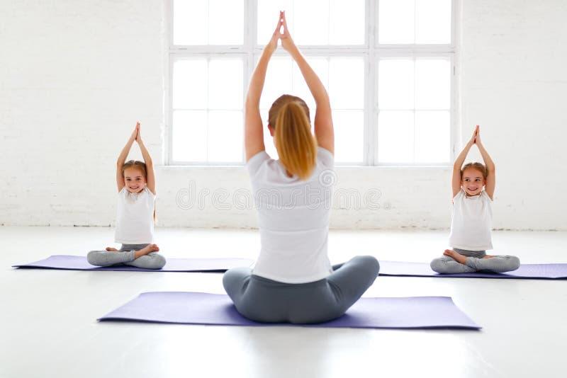 Niños que practican yoga en una actitud del loto con el profesor imagenes de archivo