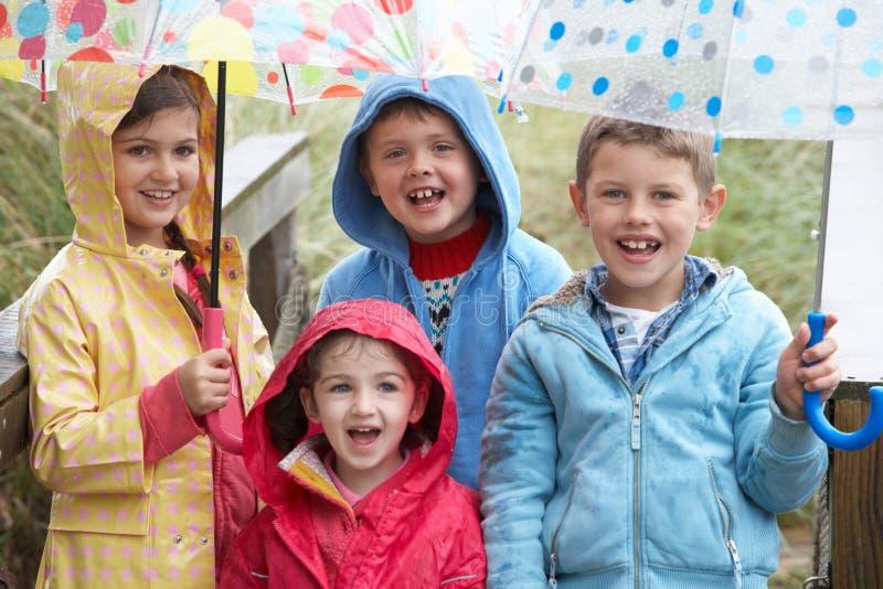 Niños que presentan con el paraguas imagen de archivo