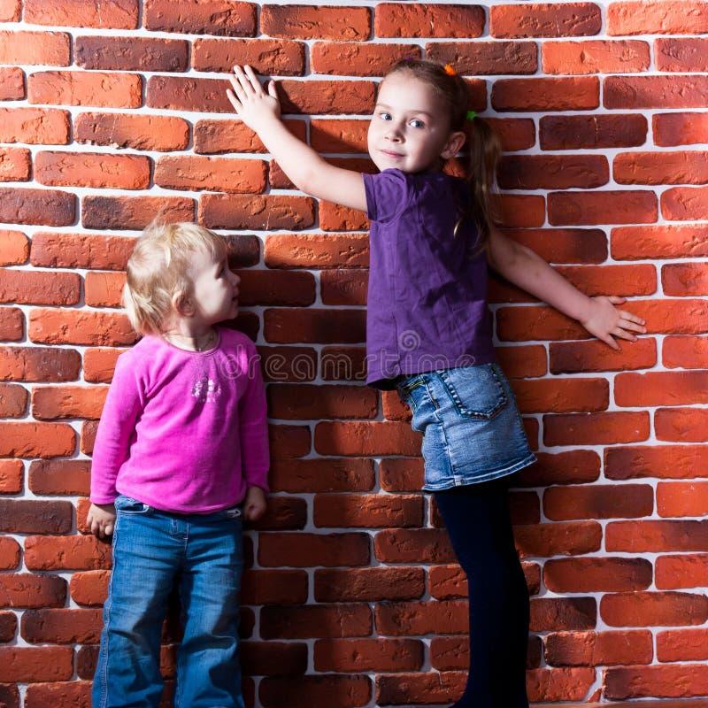 Niños que presentan contra la pared de la rotura imágenes de archivo libres de regalías