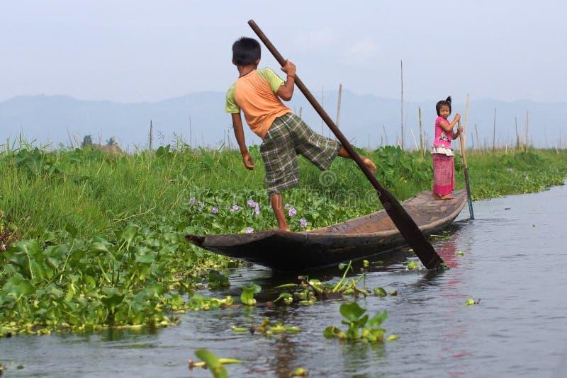 Niños que pudelan el barco en el lago Inle en Birmania, Asia imagen de archivo libre de regalías