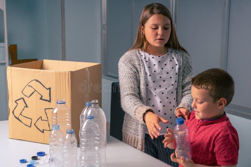 Niños que reciclan las botellas y los casquillos plásticos, actitud divertida imagen de archivo libre de regalías