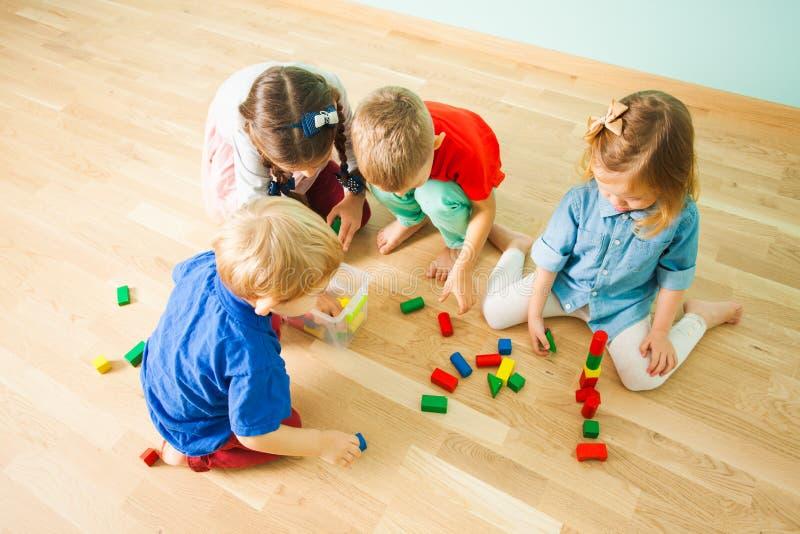 Niños que recogen los juguetes después de jugar en la guardería fotos de archivo