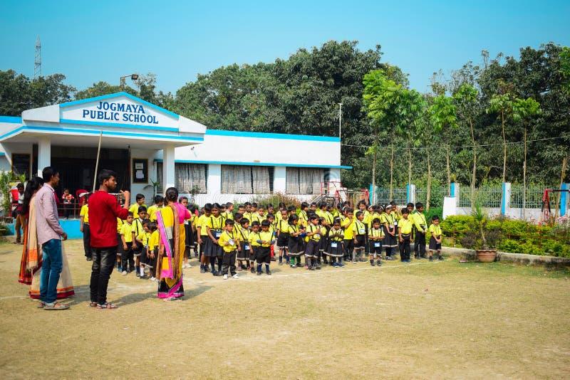 Niños que ruegan el himno nacional antes de comienzo de la escuela en uniforme delante de la construcción de escuelas con los pro fotografía de archivo