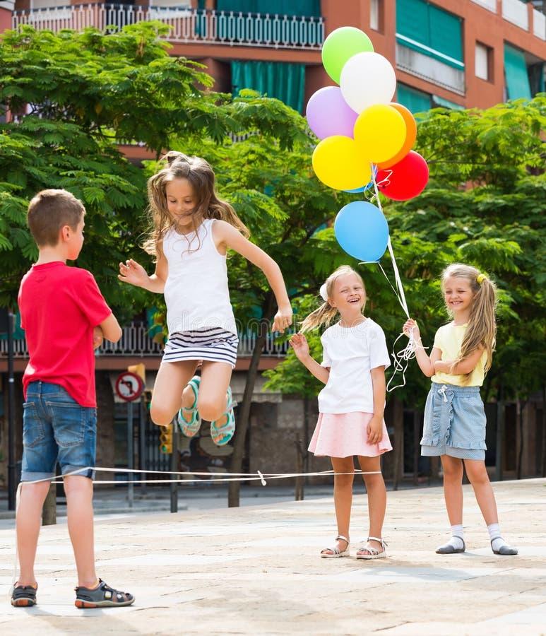 Niños que saltan en la cuerda elástico fotos de archivo