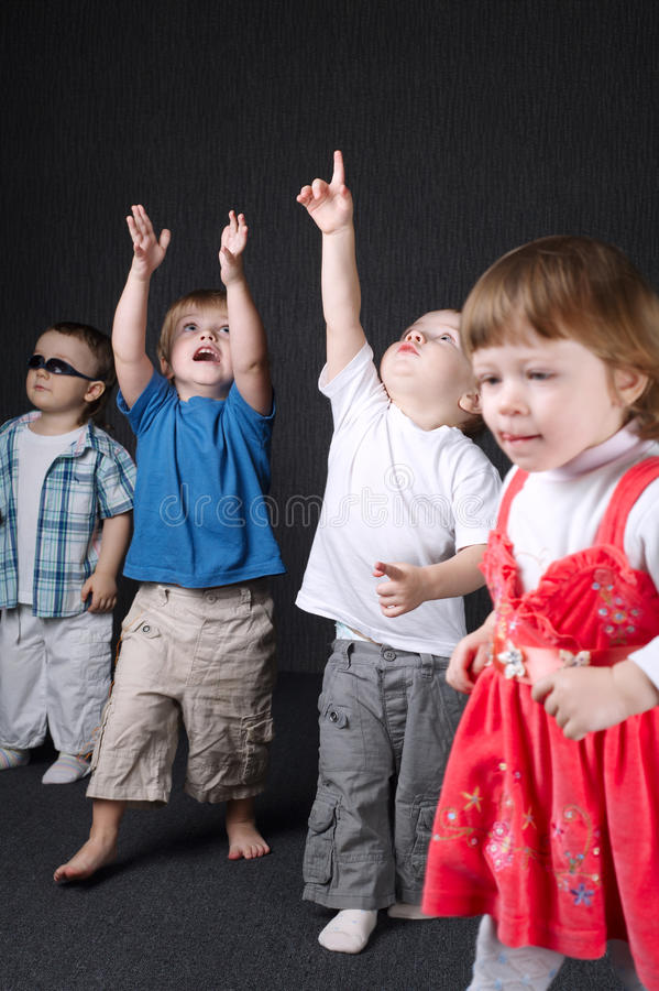 Niños que señalan para arriba en fondo oscuro imagen de archivo