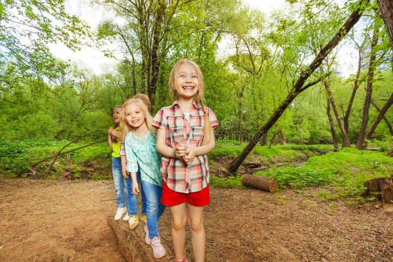 Niños que se colocan en un registro uno tras otro en bosque fotografía de archivo libre de regalías