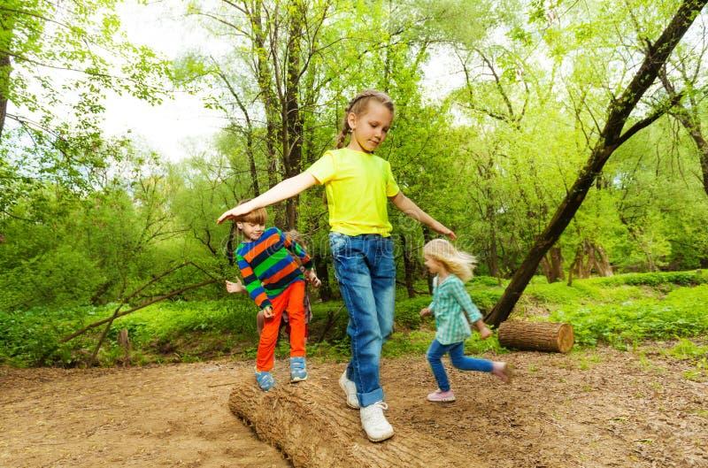 Niños que se colocan en un registro y que equilibran en el bosque imagen de archivo libre de regalías