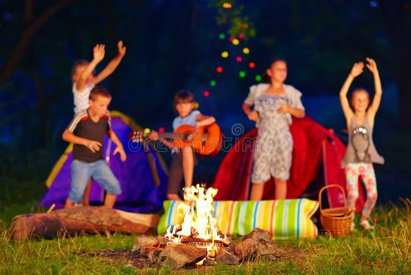 Niños que se divierten alrededor de hoguera foco en el fuego foto de archivo libre de regalías