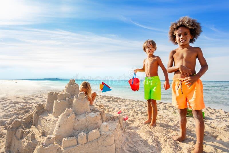 Niños que se divierten, castillo de arena del edificio en la playa foto de archivo