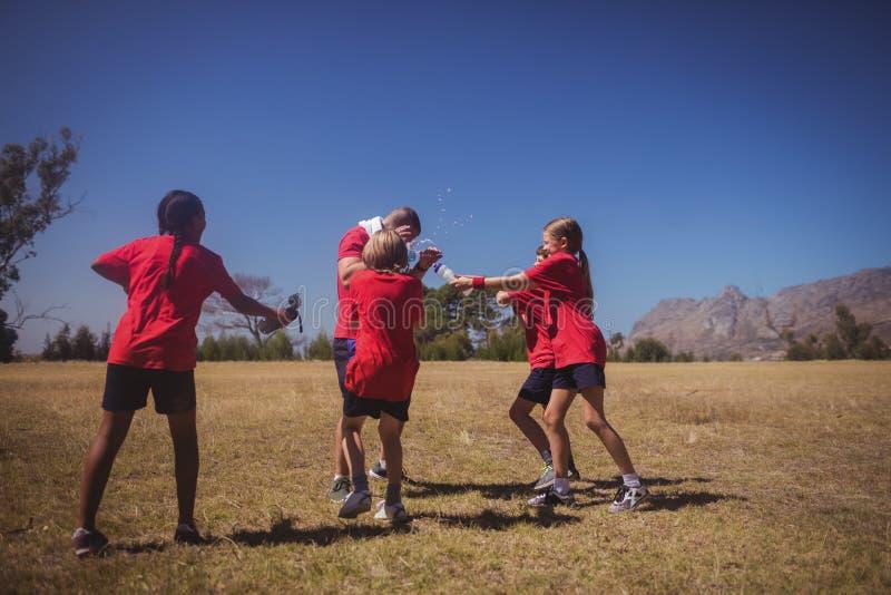 Niños que se divierten con el instructor en el campo de bota foto de archivo