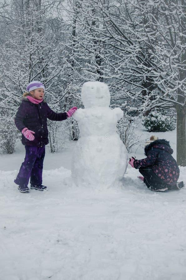 Niños que se divierten que construye un muñeco de nieve en parque del invierno fotos de archivo
