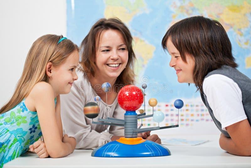 Niños que se divierten que estudia la Sistema Solar fotos de archivo