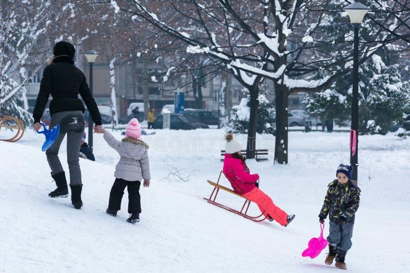 Niños que se divierten y sledding en las colinas en parque público fotos de archivo