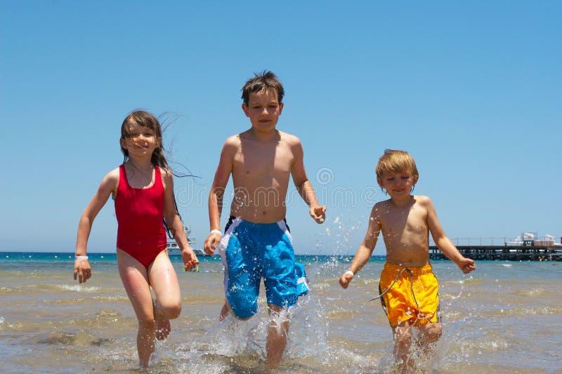 Niños que se ejecutan en agua foto de archivo libre de regalías