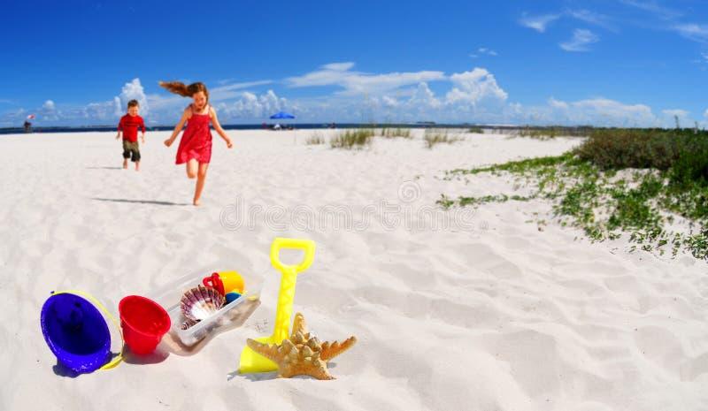 Niños que se ejecutan hacia los juguetes de la playa fotos de archivo libres de regalías