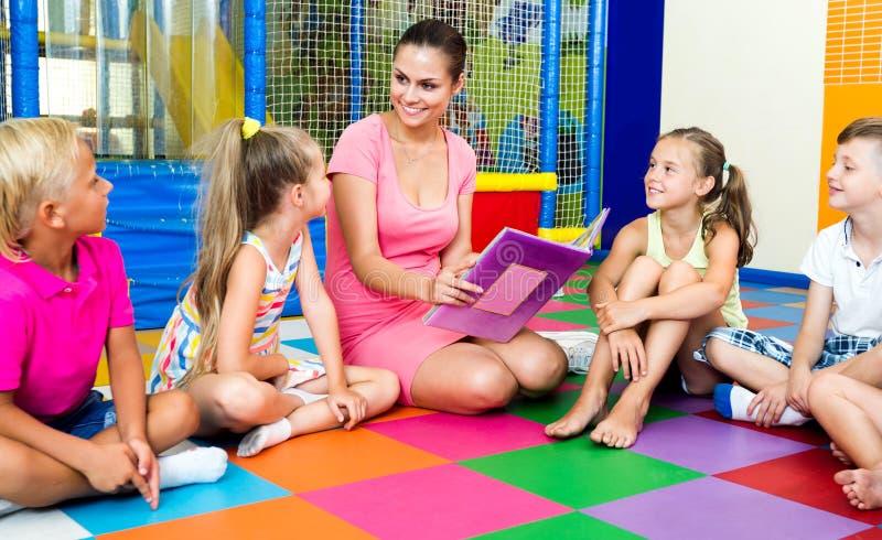 Niños que se sientan alrededor del libro de lectura del profesor imagenes de archivo