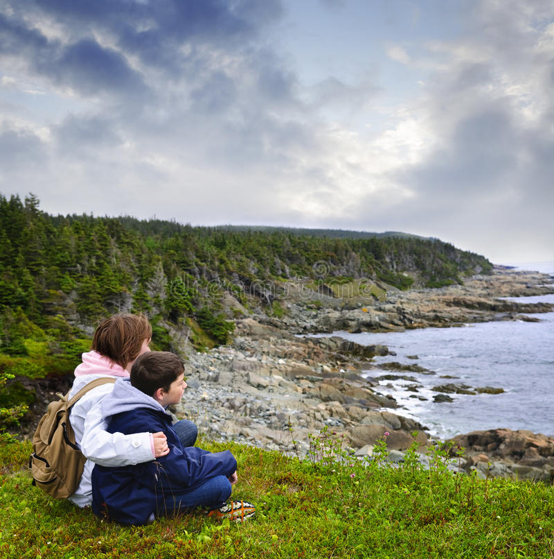 Niños que se sientan en la costa atlántica en Terranova imágenes de archivo libres de regalías