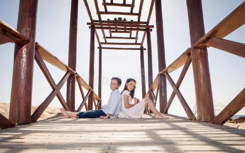 Niños que se sientan en la estructura de madera en la playa imagenes de archivo