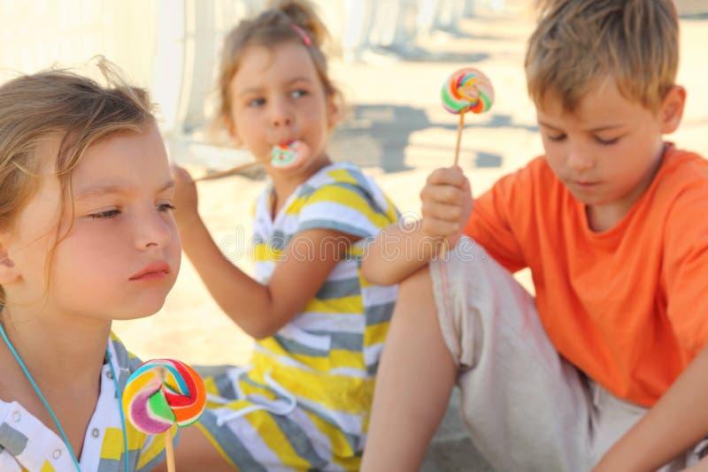 Niños que se sientan en la playa y que comen los lollipops fotografía de archivo