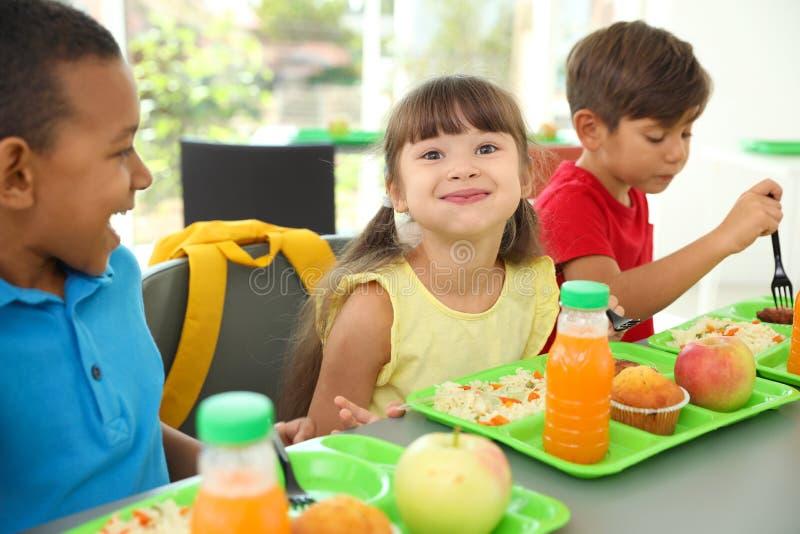 Niños que se sientan en la tabla y que comen la comida sana durante rotura fotografía de archivo libre de regalías