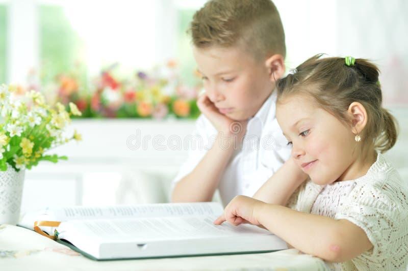 Niños que se sientan en la tabla y la lectura imagenes de archivo