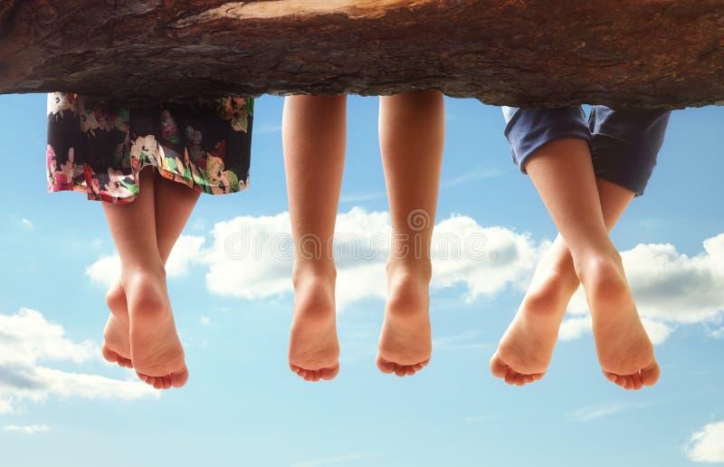 Niños que se sientan en un árbol que cuelga sus pies imágenes de archivo libres de regalías