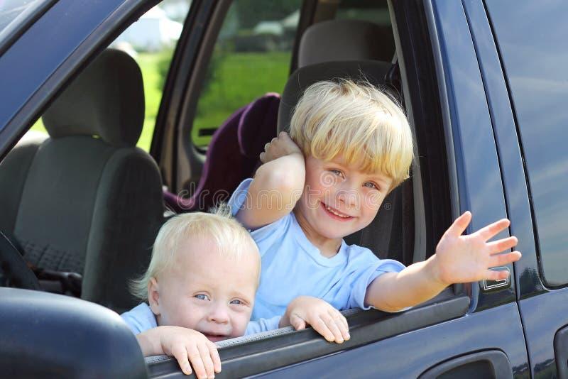 Niños que sonríen hacia fuera Van Window fotos de archivo