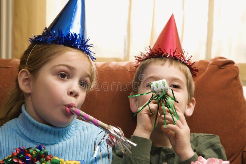 Niños que soplan noisemakers. fotografía de archivo