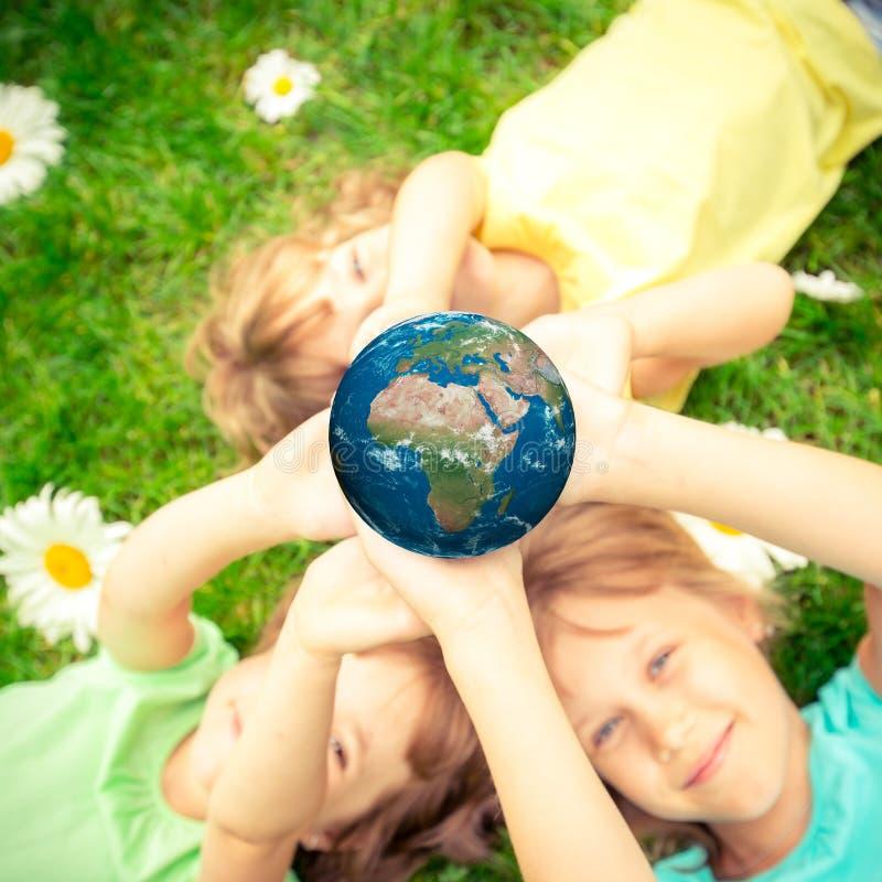 Niños que sostienen el planeta de la tierra en manos fotografía de archivo libre de regalías