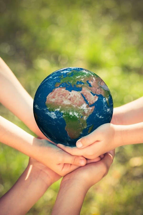 Niños que sostienen el planeta de la tierra en manos fotos de archivo