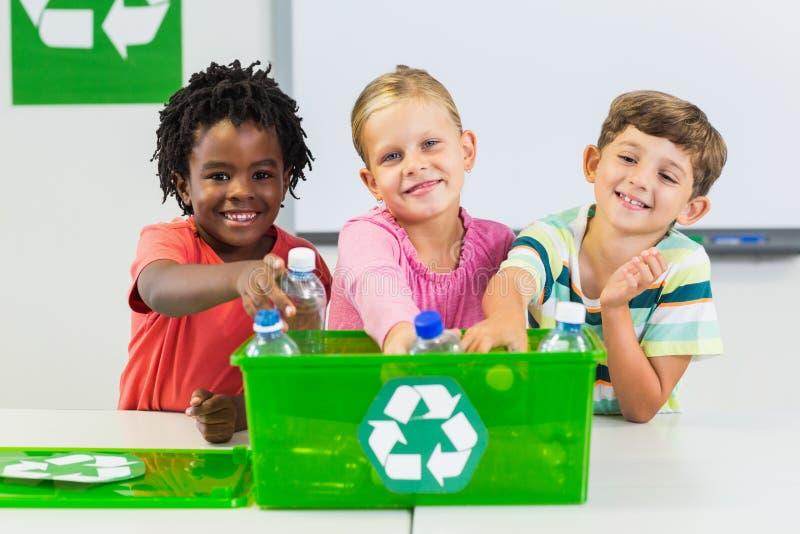 Niños que sostienen la botella reciclada en sala de clase imagen de archivo