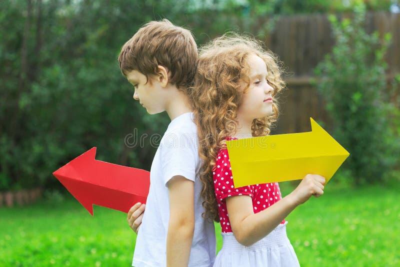Niños que sostienen la flecha del color que señala a la derecha y a la izquierda, en verano fotografía de archivo libre de regalías