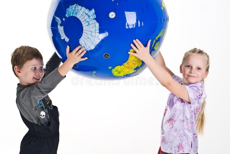 Niños que sostienen la tierra fotografía de archivo libre de regalías