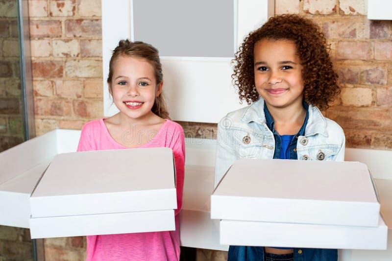 Niños que sostienen las cajas de la pizza fotos de archivo