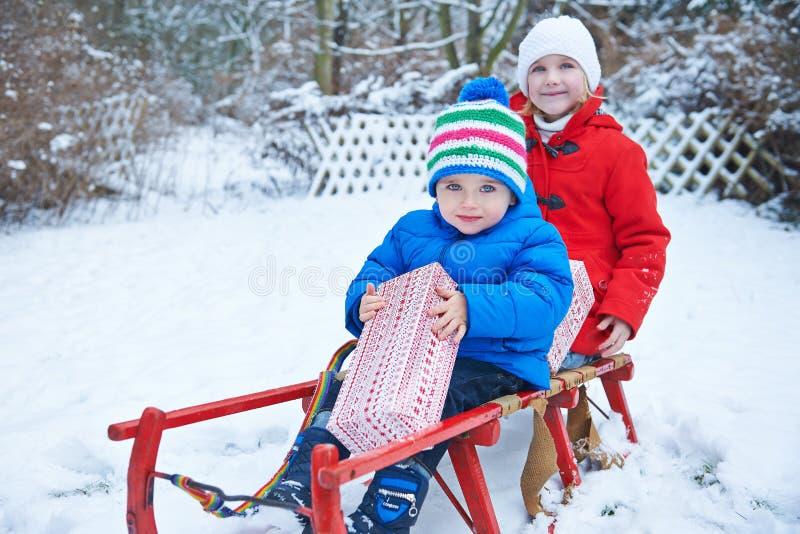 Niños que sostienen los regalos de la Navidad en el trineo en invierno imagen de archivo