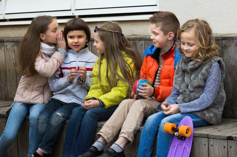 Niños que susurran en otros oídos al aire libre imágenes de archivo libres de regalías