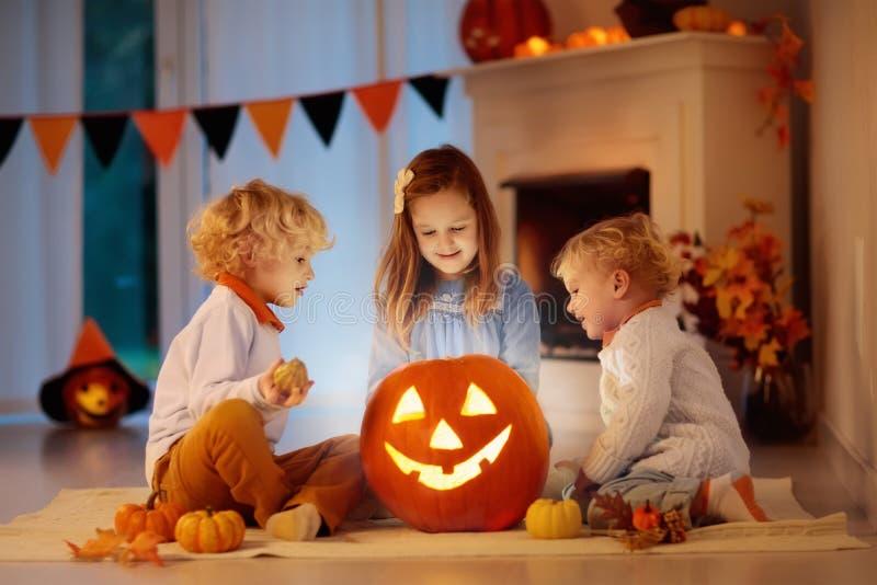 Niños que tallan la calabaza en Halloween Truco o convite fotografía de archivo