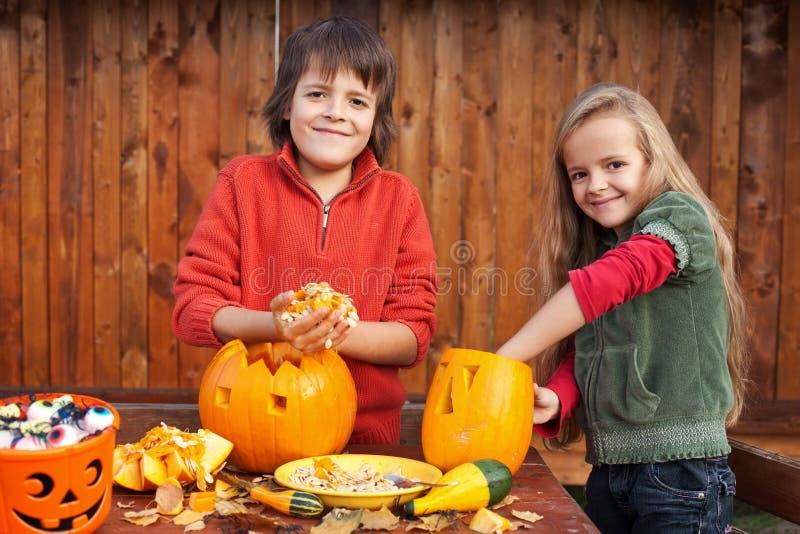 Niños que tallan sus Jack-o-linternas de la calabaza fotografía de archivo libre de regalías