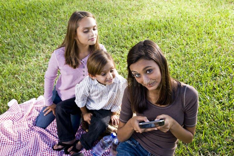 Niños que tienen comida campestre en el parque que juega con el smartp imagen de archivo libre de regalías
