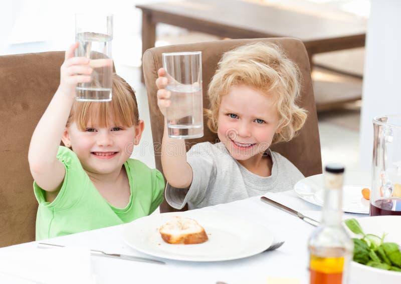Niños que tuestan con su bebida imagen de archivo