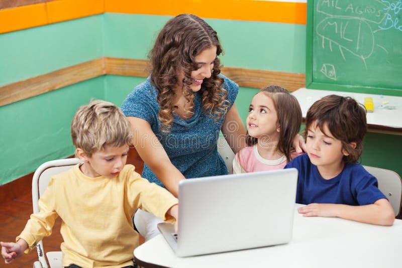 Niños que usan el ordenador portátil mientras que profesor Assisting Them imagen de archivo
