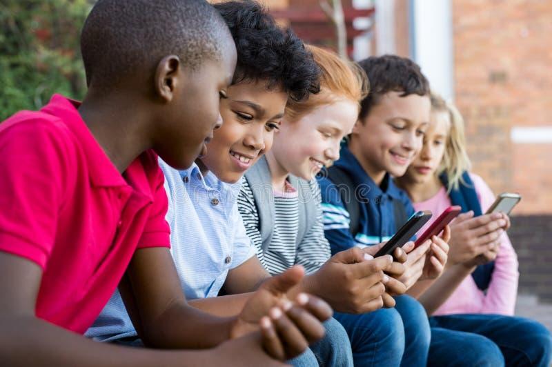 Niños que usan el teléfono elegante fotos de archivo libres de regalías