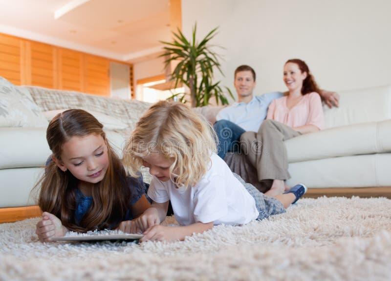 Niños que usan la tableta en la alfombra imágenes de archivo libres de regalías