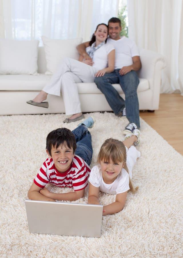 Niños que usan una computadora portátil en suelo en sala de estar imágenes de archivo libres de regalías