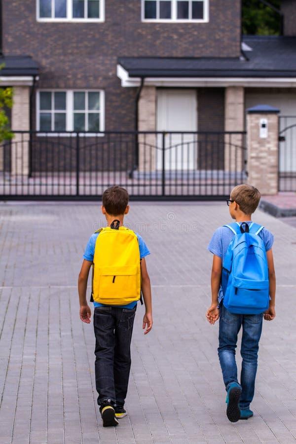 Niños que van a casa de escuela Visión posterior imagen de archivo